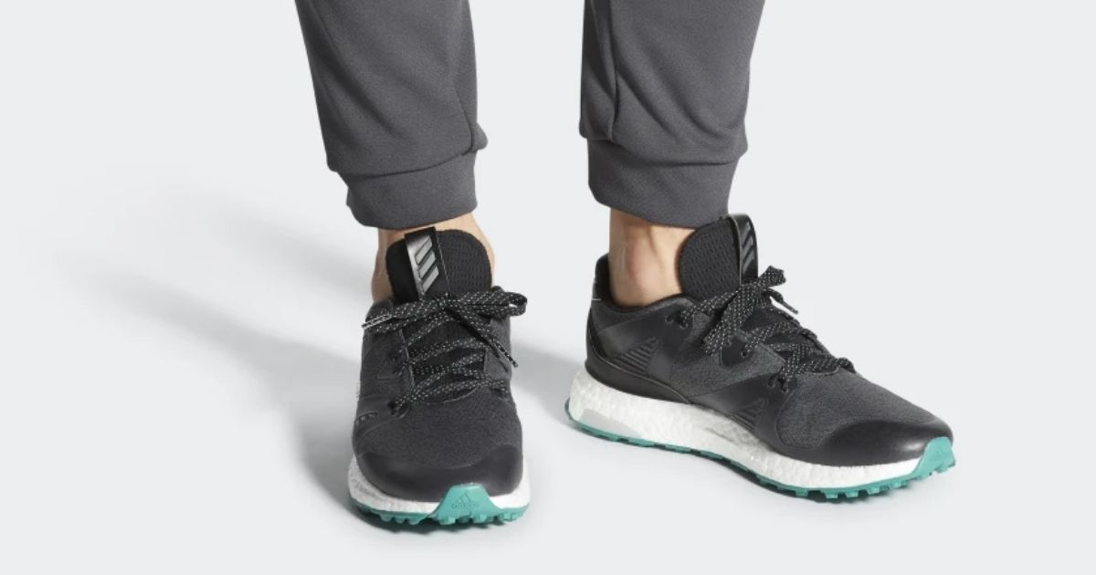 bottom part of mens legs wearing black and gray adidas shoes with teal bottom