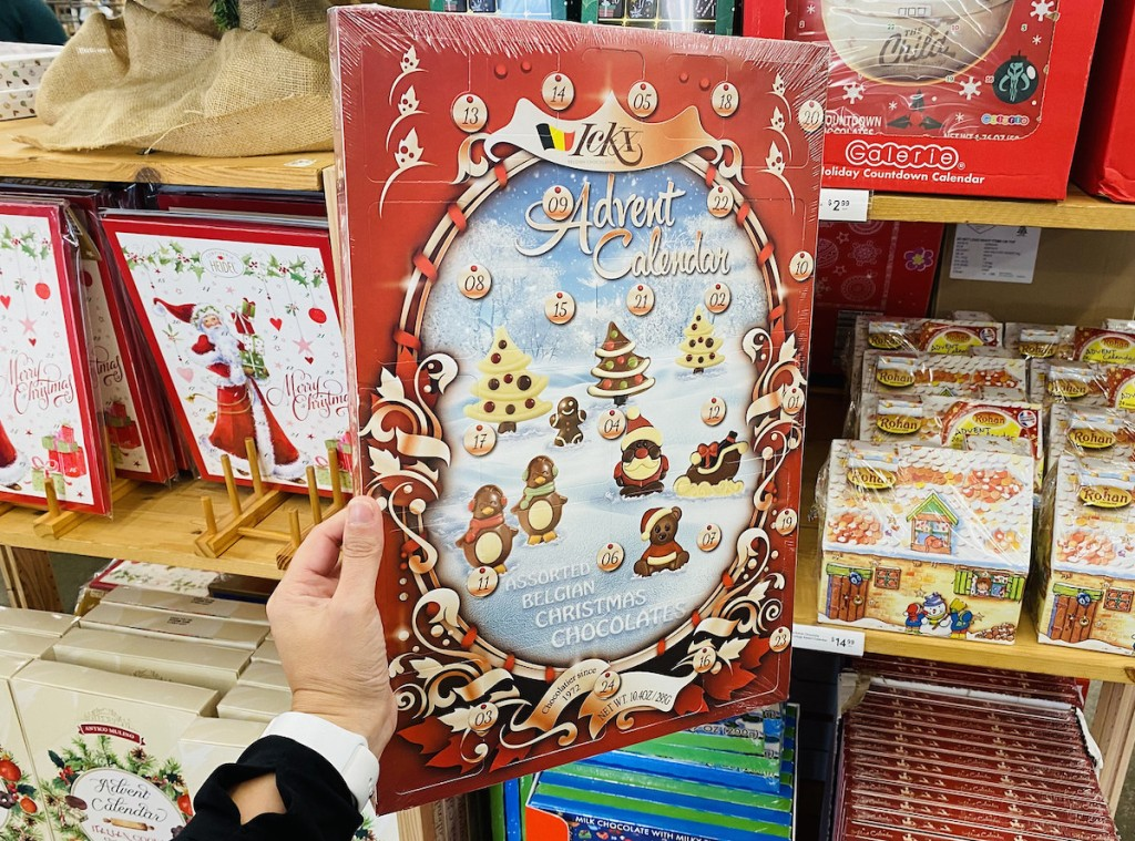 hand holding a chocolate advent calendar in front of store shelf