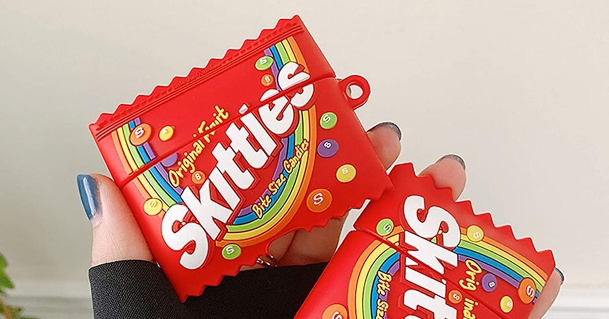 memegang kotak AirPods yang berbentuk seperti paket Skittles
