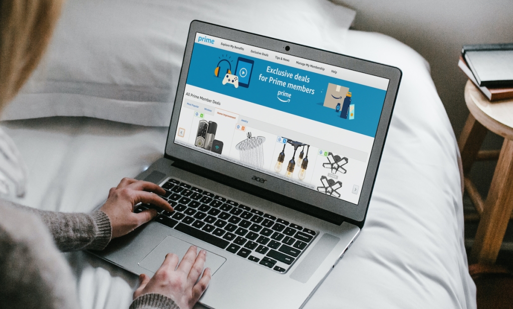 hands typing on laptop with amazon prime day exclusive deals on screen