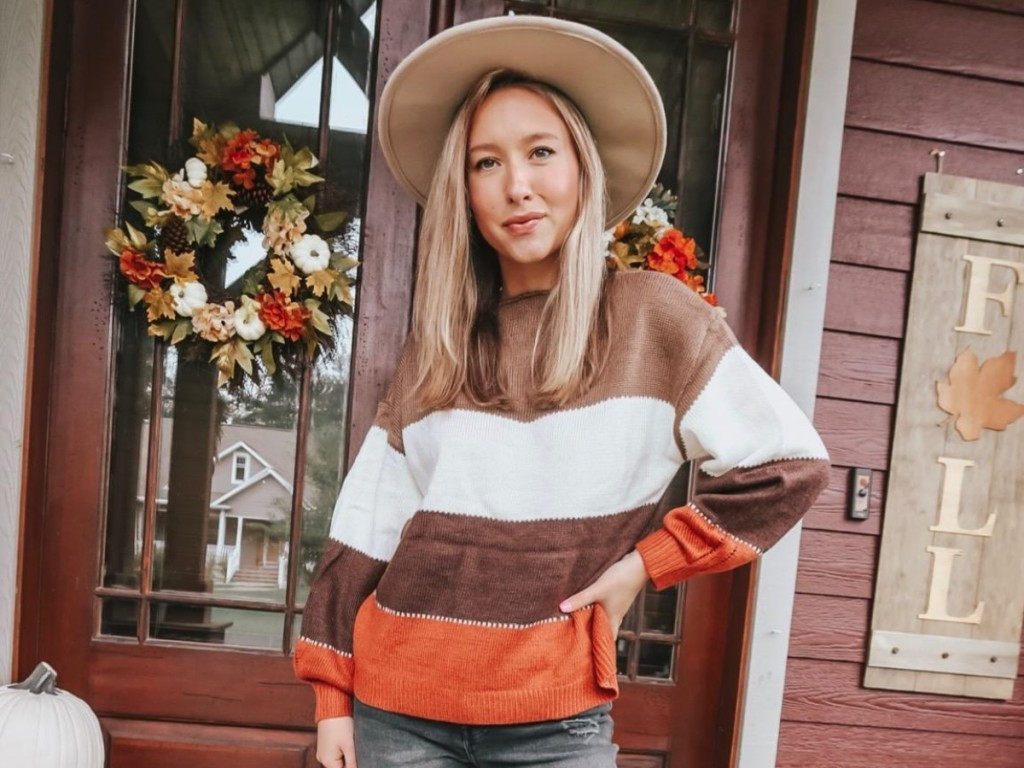 woman wearing sweater and hat in front of home