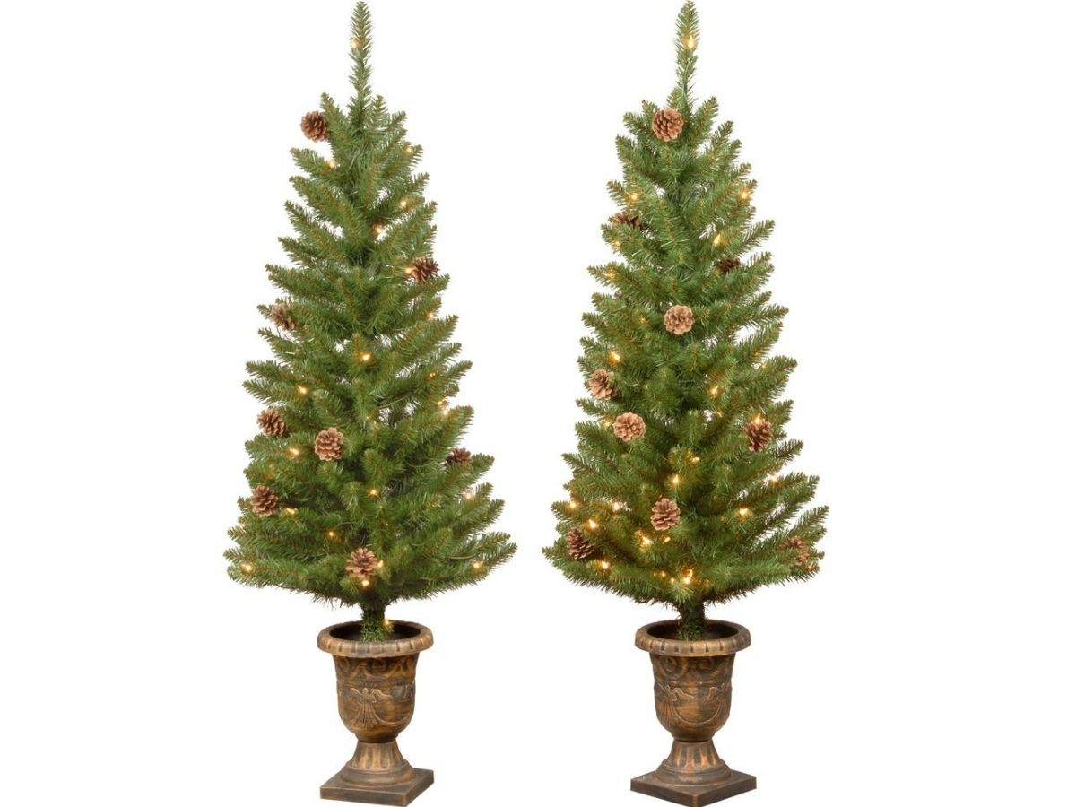 2 artificial Christmas trees in gold pots