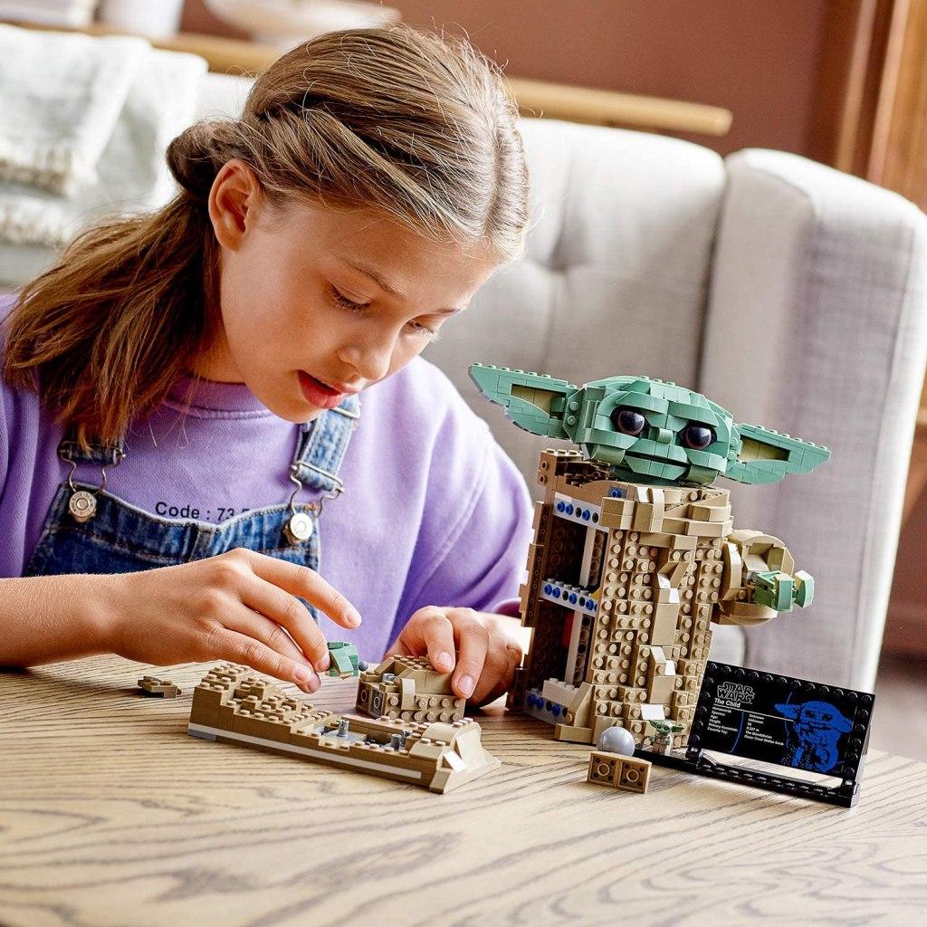 little girl building baby yoda lego