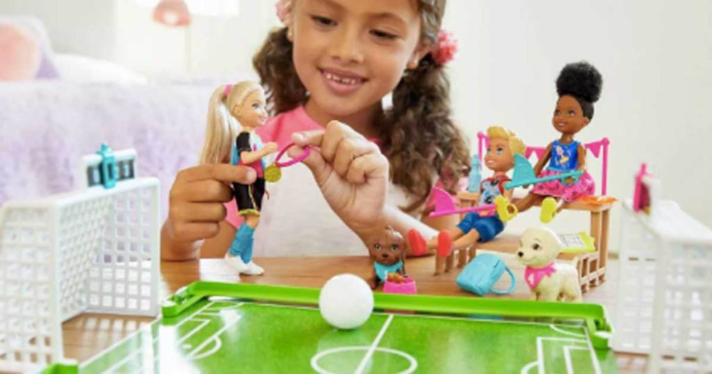 little girl playing with a barbie set