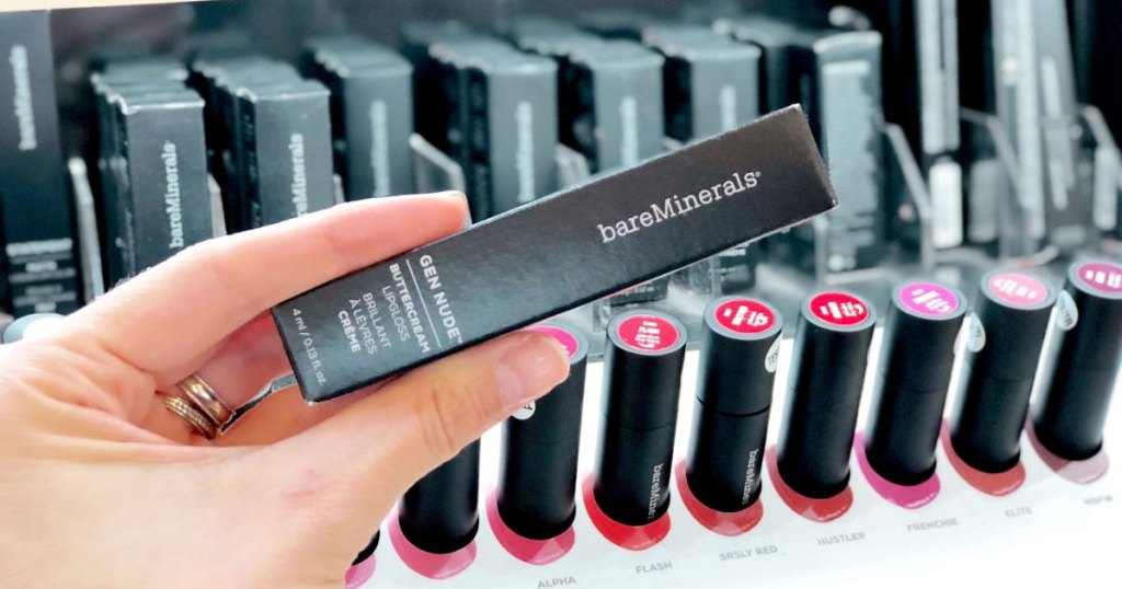 woman holding up black box for bareMinerals lipstick in front of a lipstick display
