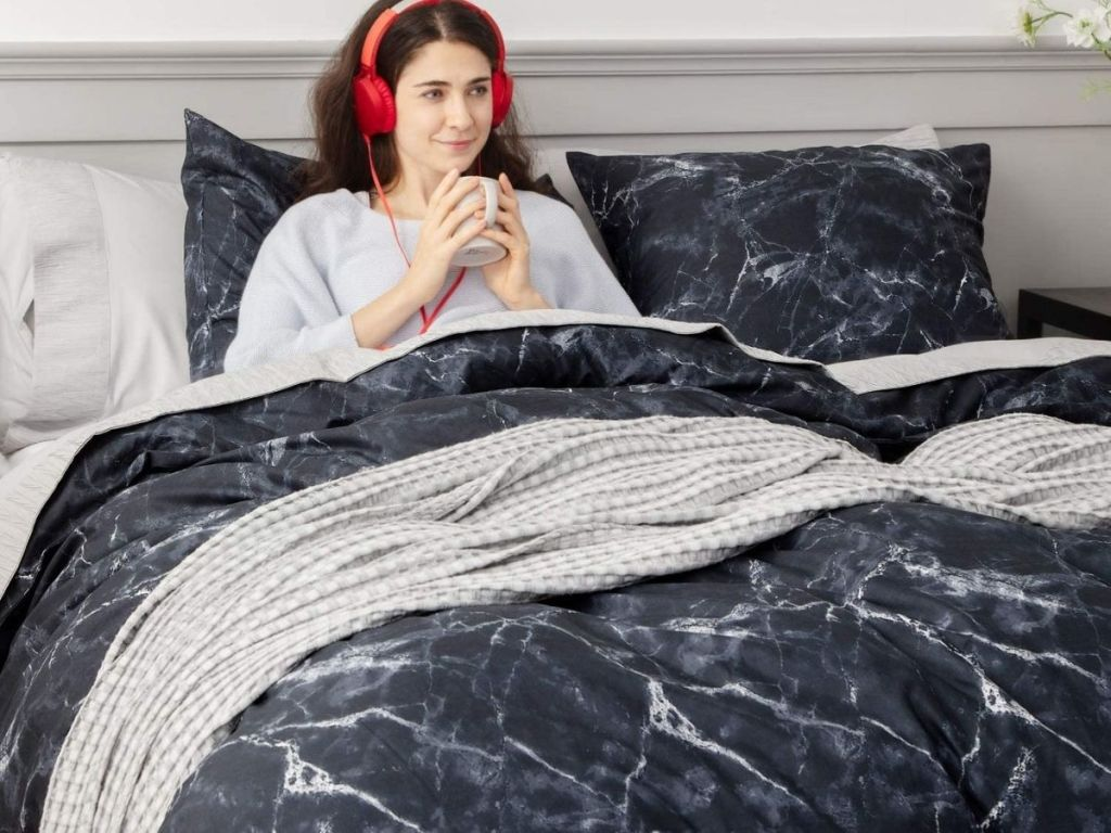 woman sitting in bed with black marble duvet on her