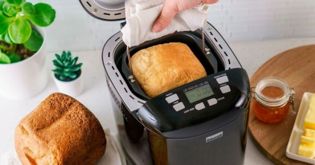 top view of hand taking bread loaf out of bella bread maker
