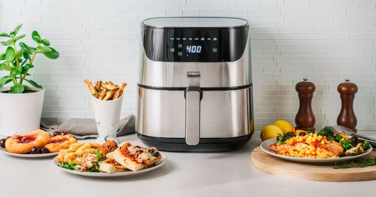 stainless steel Bella air fryer with plates of food surrounding machine