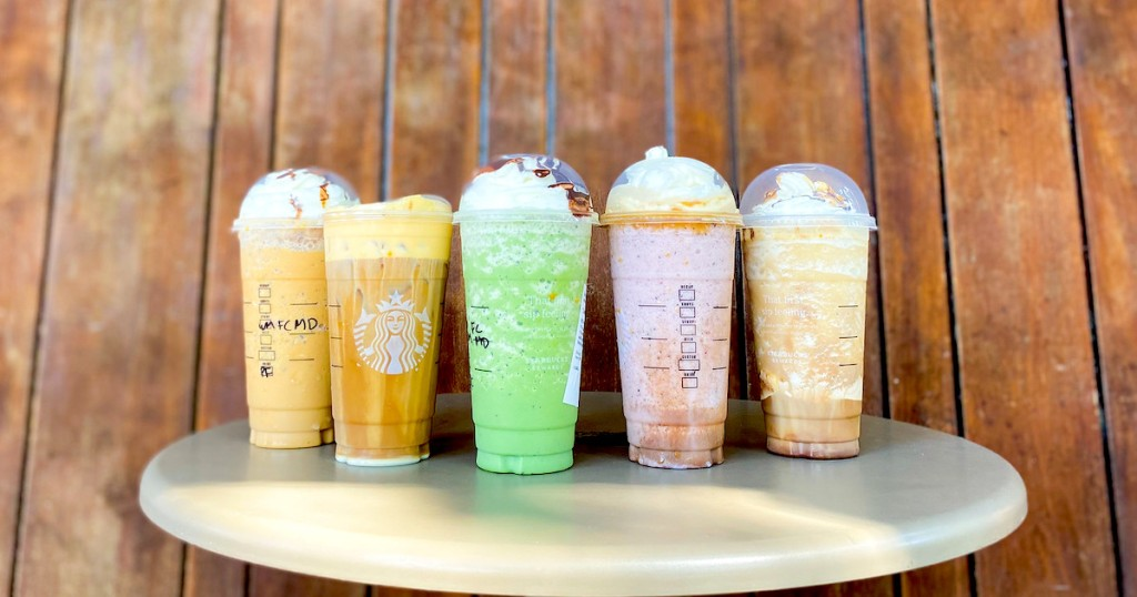 row of various kinds of starbucks drinks on table in front of wood wall