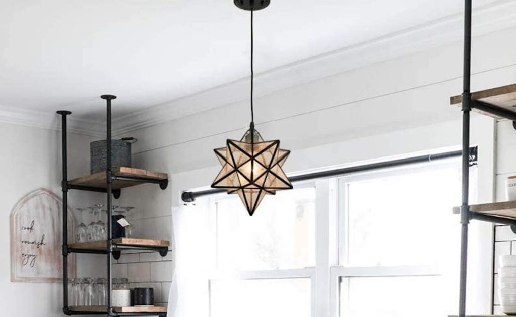 black star pendant light hanging in front of kitchen window