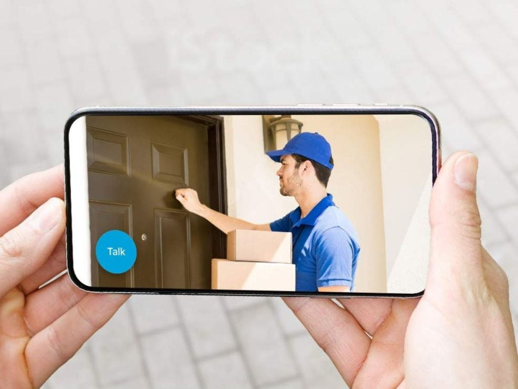 hand holding phone showing delivery man at door