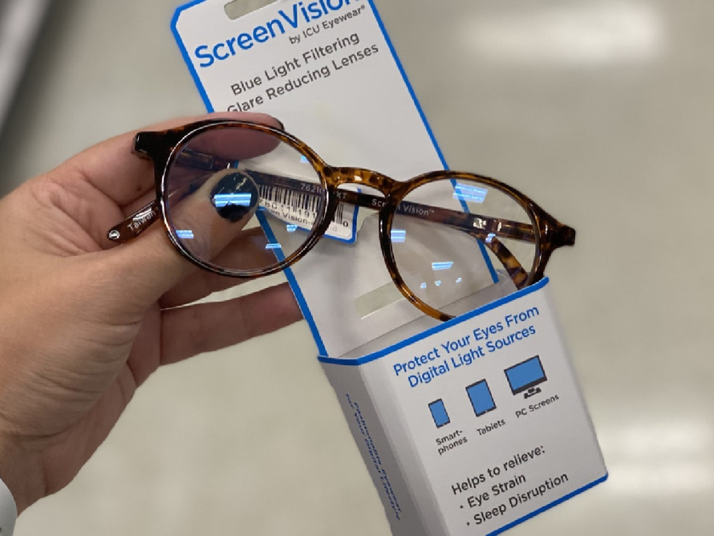 hand holding pair of glasses connected to packaging