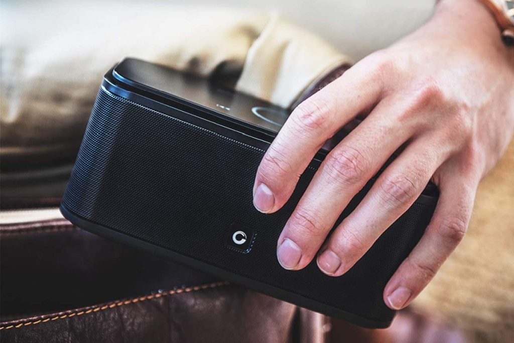 bluetooth portable speaker DOSS in hand going into pocket