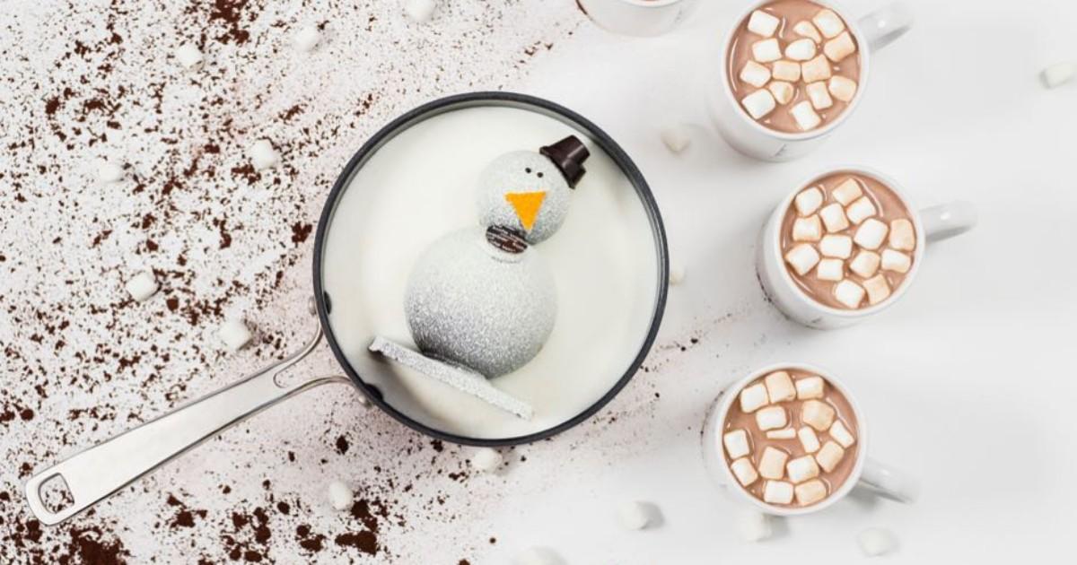 snowman cocoa bomb in pot of milk