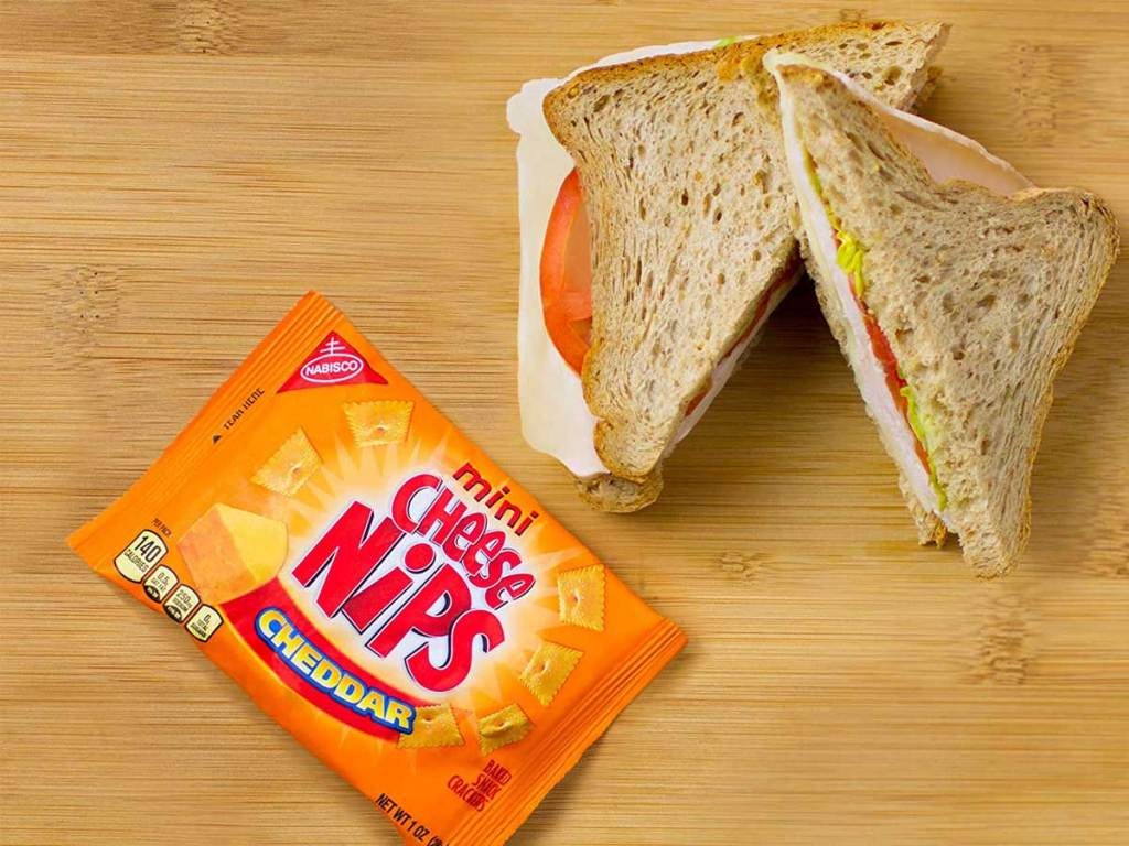 Cheese nips snack bag next to sandwich