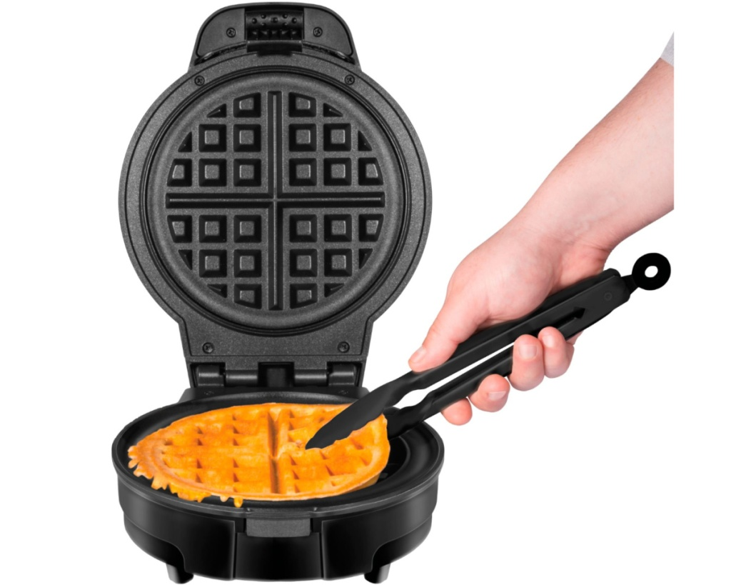 hand using tongs to grab waffle from chefman waffle maker