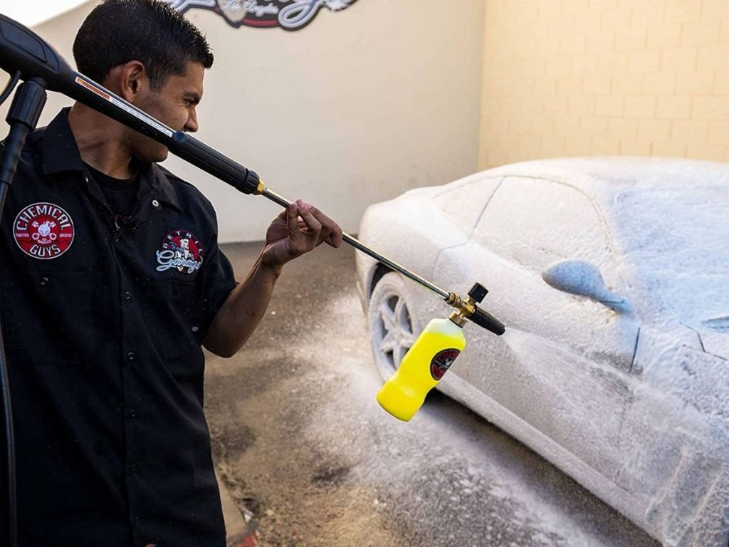 man washing car with car wash spray