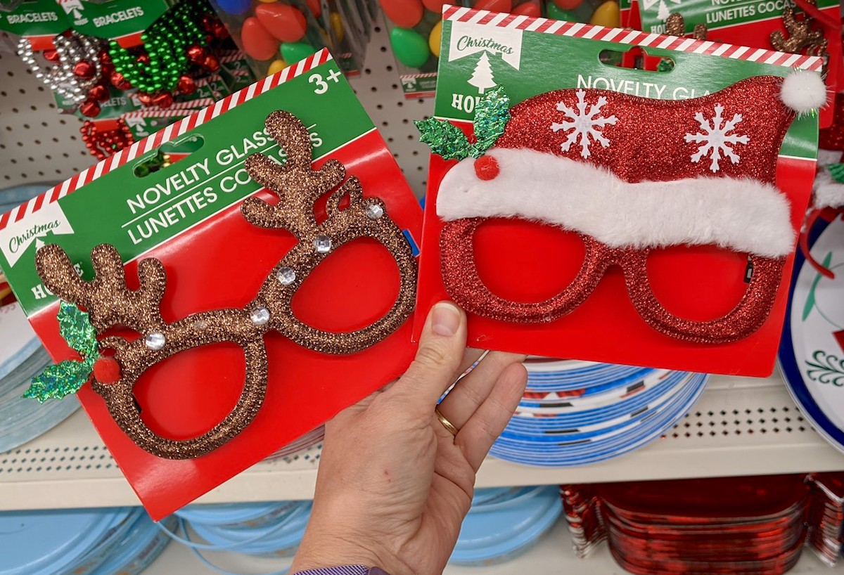 hand holding reindeer and santa hat glasses prop in dollar tree christmas decorations aisle
