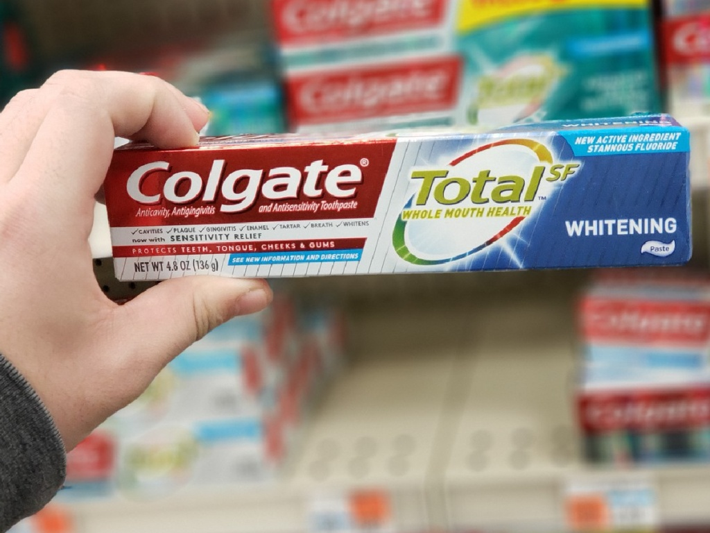 hand holding up box of toothpaste at store
