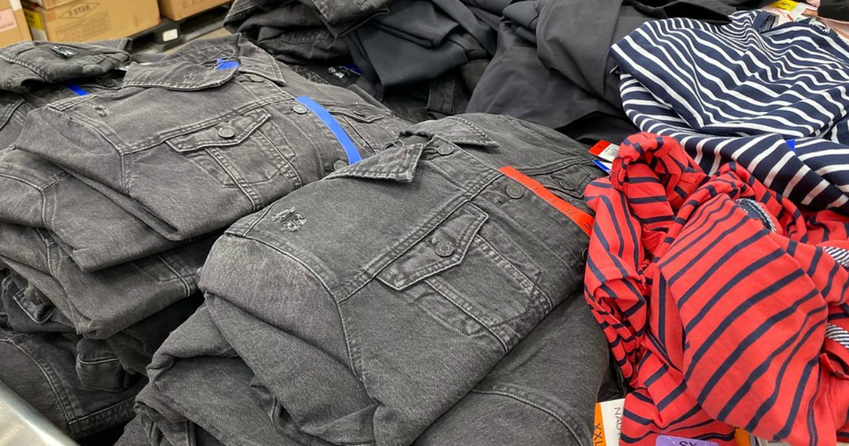 stacks of denim jackets and shirts on a table
