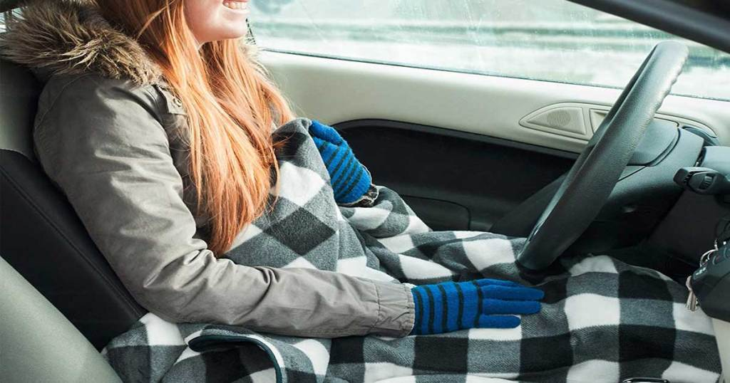 person sitting in a car with an electric blanket
