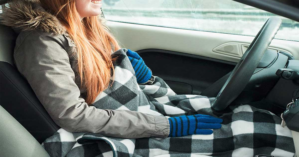 woman sitting in car with plaid blanket on her lap
