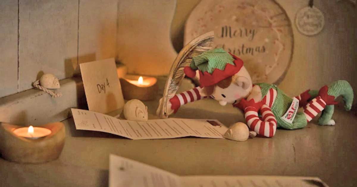elf laying on table writing a letter