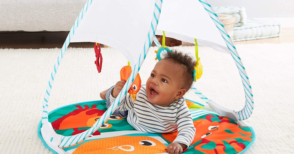 baby playing on fisher price foldable playmat