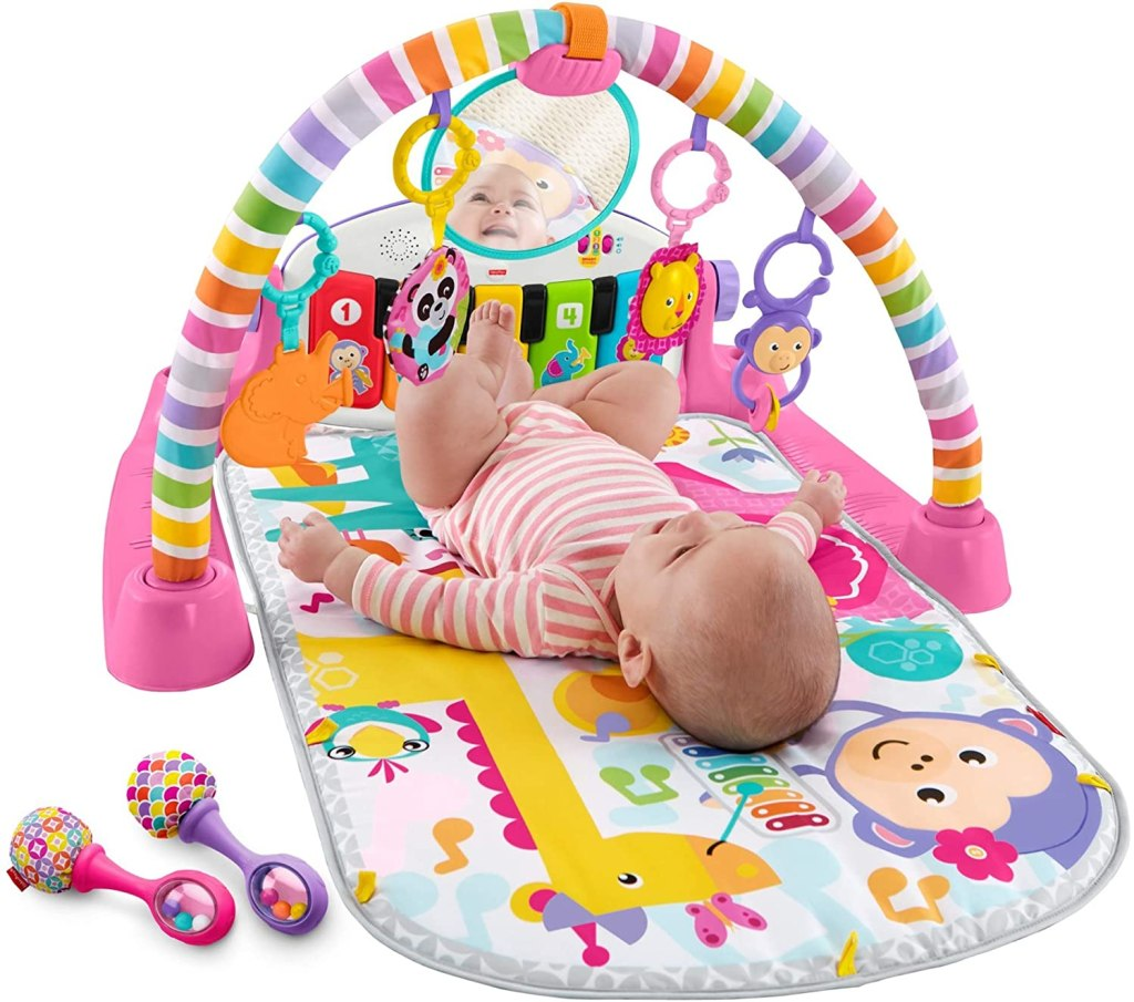 baby laying under pink playmat