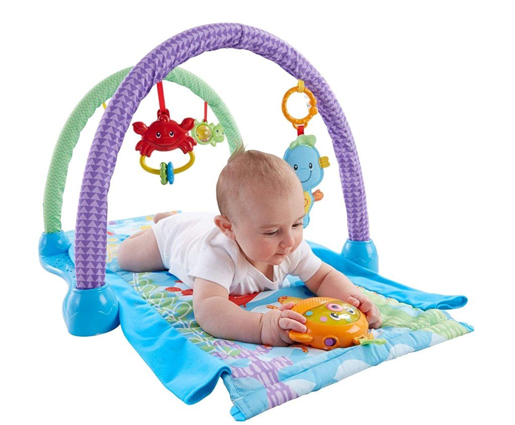 baby playing under playmat