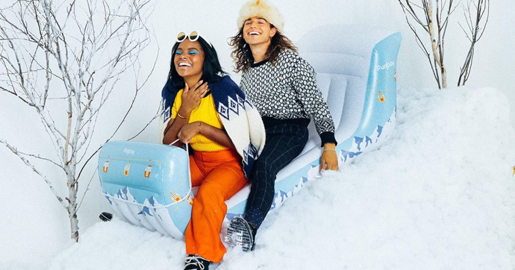 2 people smiling on a inflatable sleigh on snow covered hill