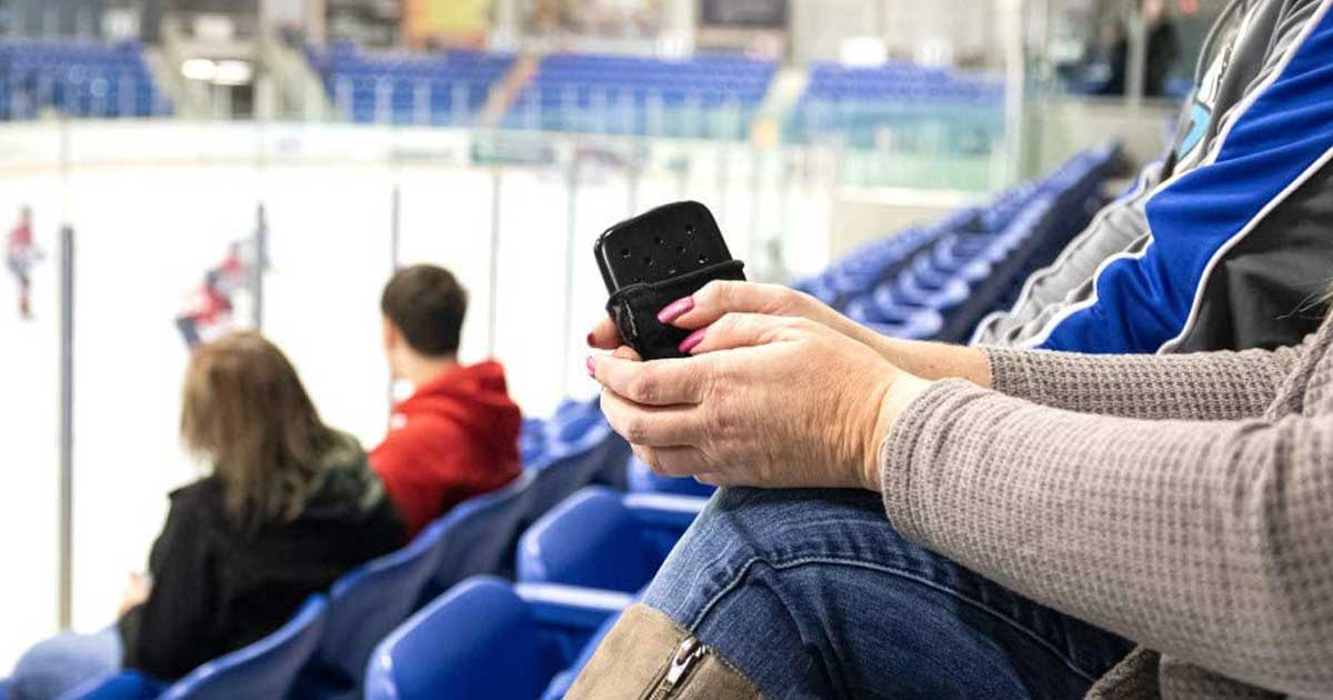 woman sitting at hockey game with hand warmer