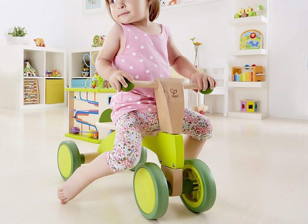 little girl on hape wood bike