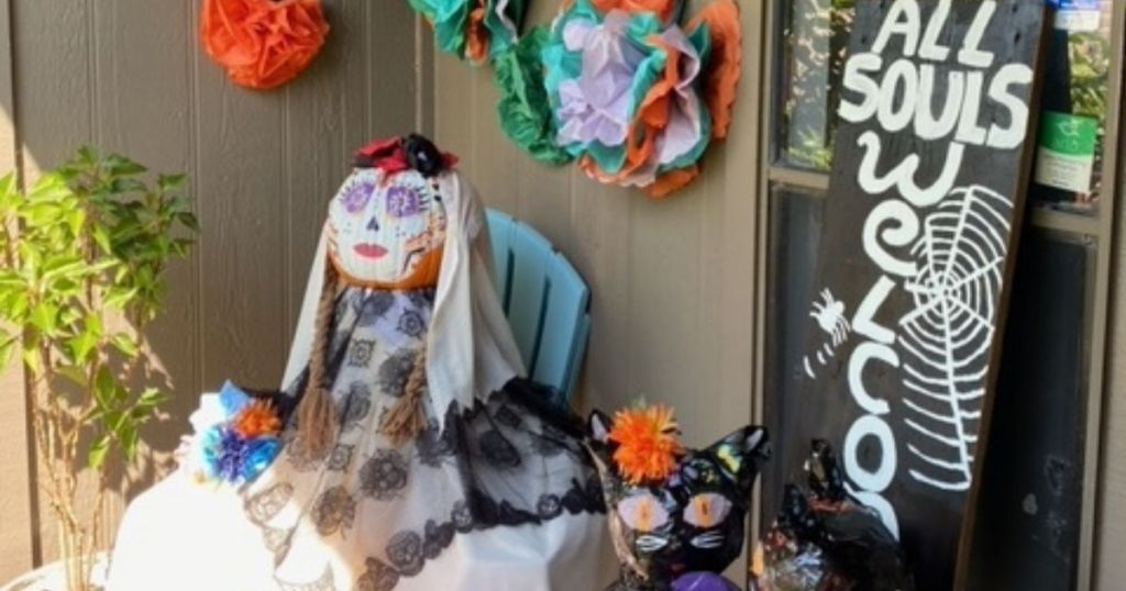 Halloween display on porch featuring pumpkin woman, black cats and tissue flowers