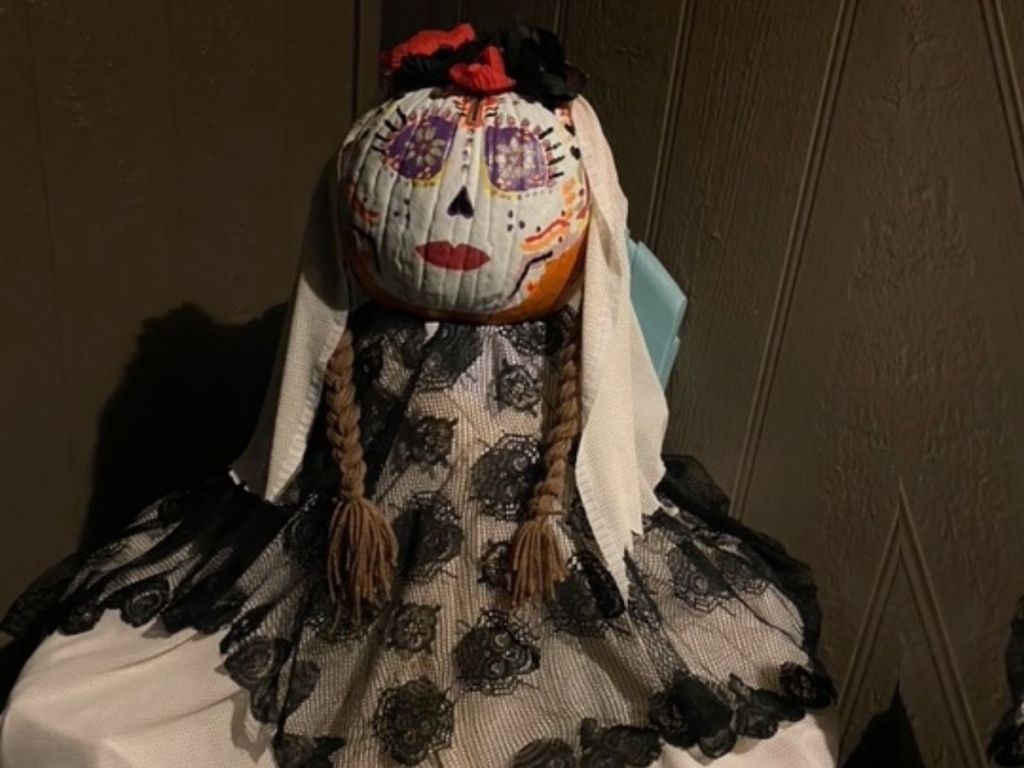 pumpkin painted with face and dressed in freaky clothing