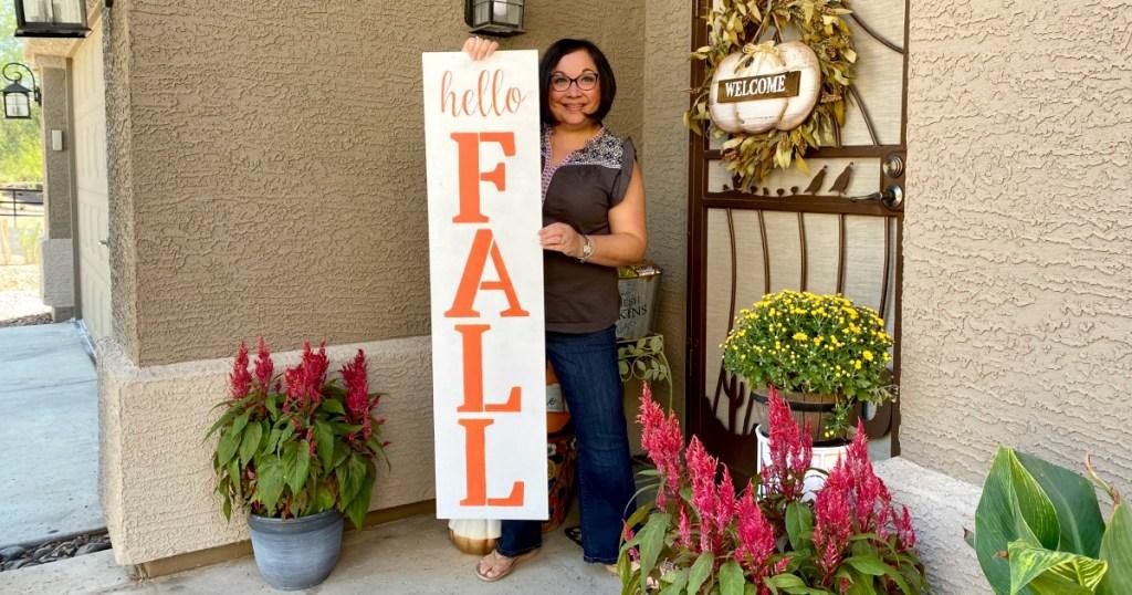 woman holding DIY hello fall porch sign