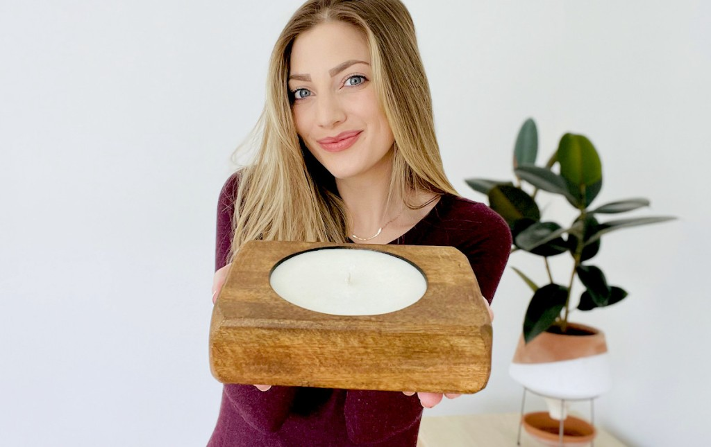 woman holding out candle with plant in background