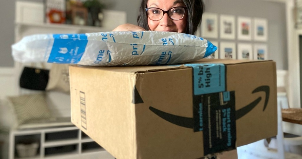 Woman holding packages with Amazon logo