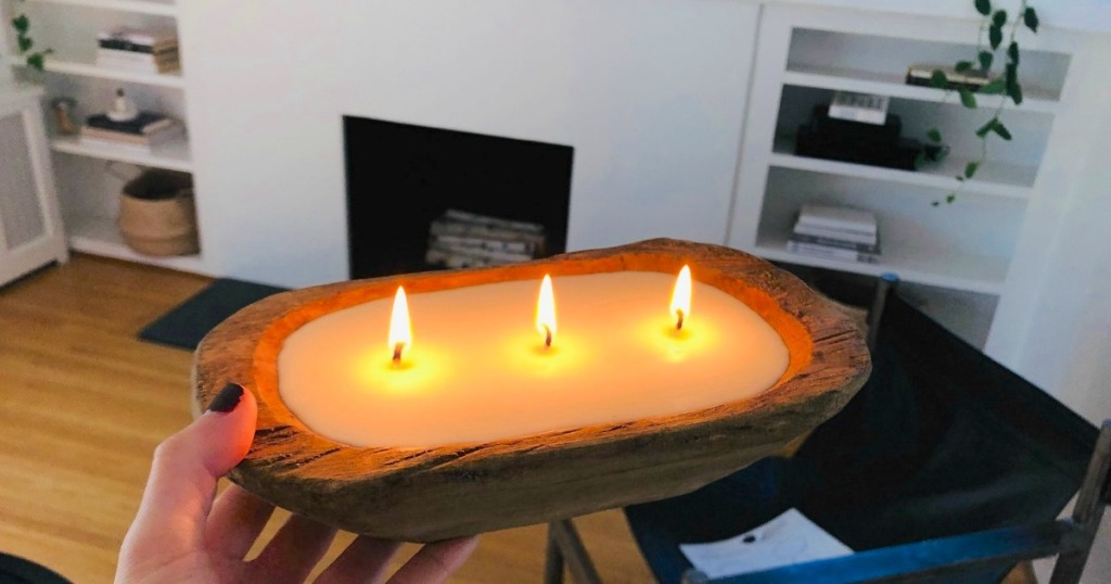 holding wood candle that's burning