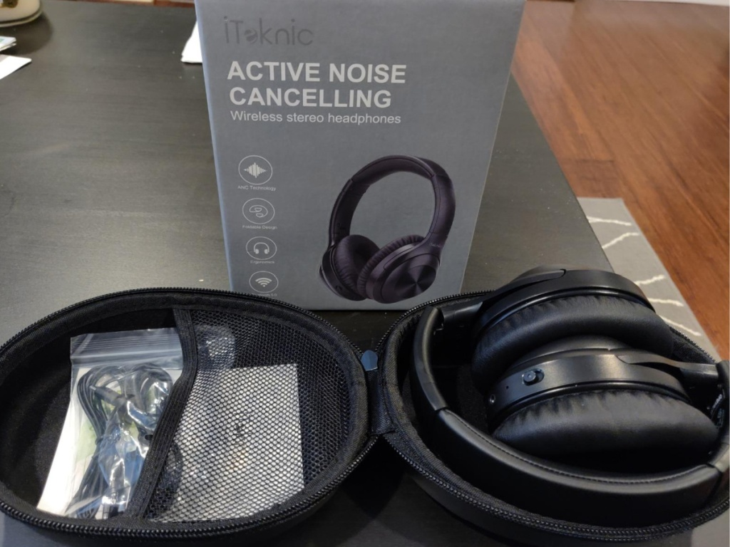 iTeknic Noise Canceling Headphones sitting in a carrying case with cord and to the box