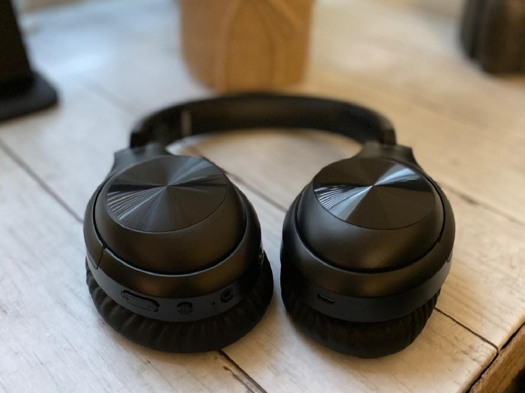 iTeknic Noise Canceling Headphones sitting open on a table in front of a plant