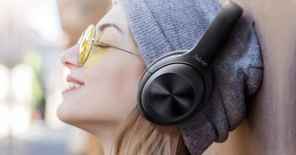 girl wearing yellow glasses and a grey beanie hat with wireless black headphones