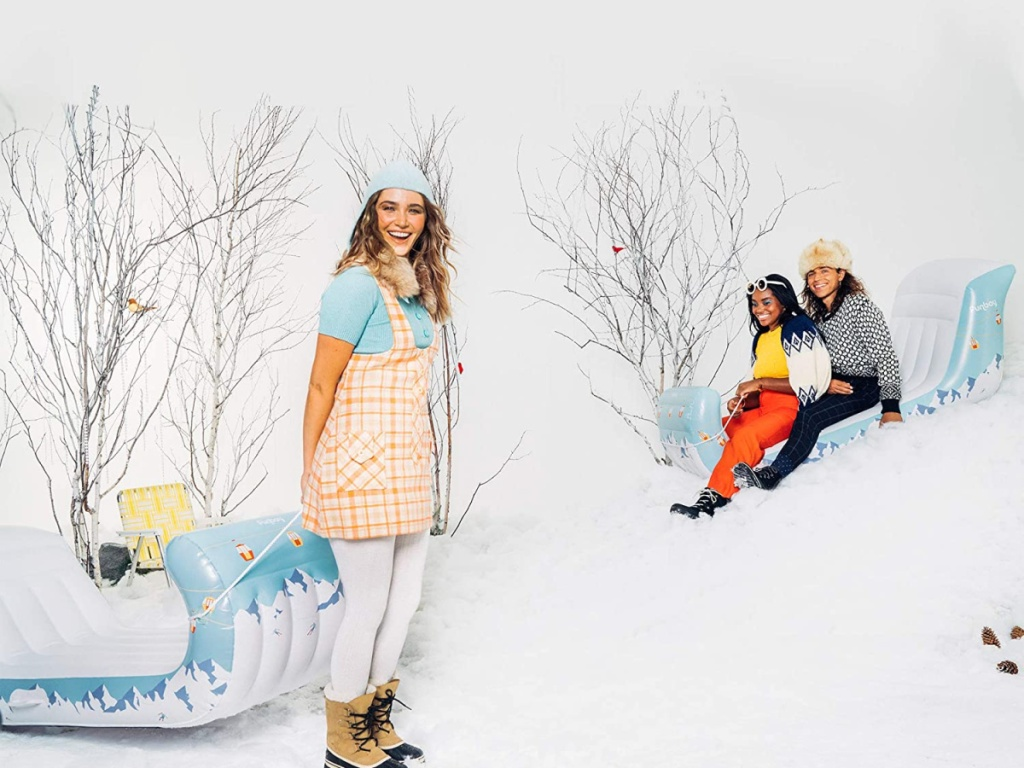 people on snow covered hill with sleighs