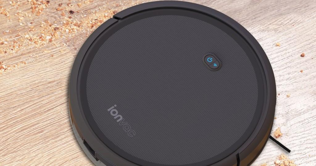 black smart vacuum on dirty hardwood floor