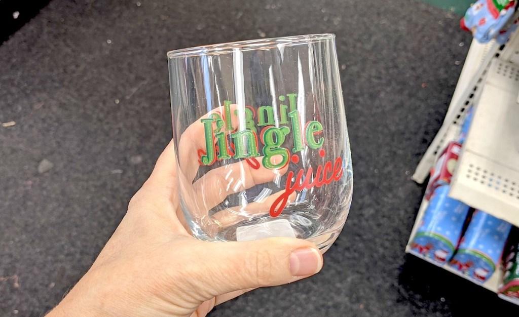 hand holding jingle juice stemless wine glass