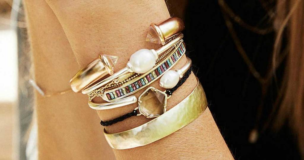 woman holding up wrist with gold bracelets