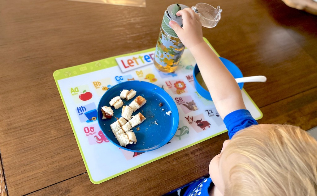 toddler kid grabbing sippy cup with food on blue plate