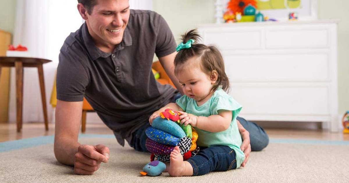 baby on floor with grown up playing with ball