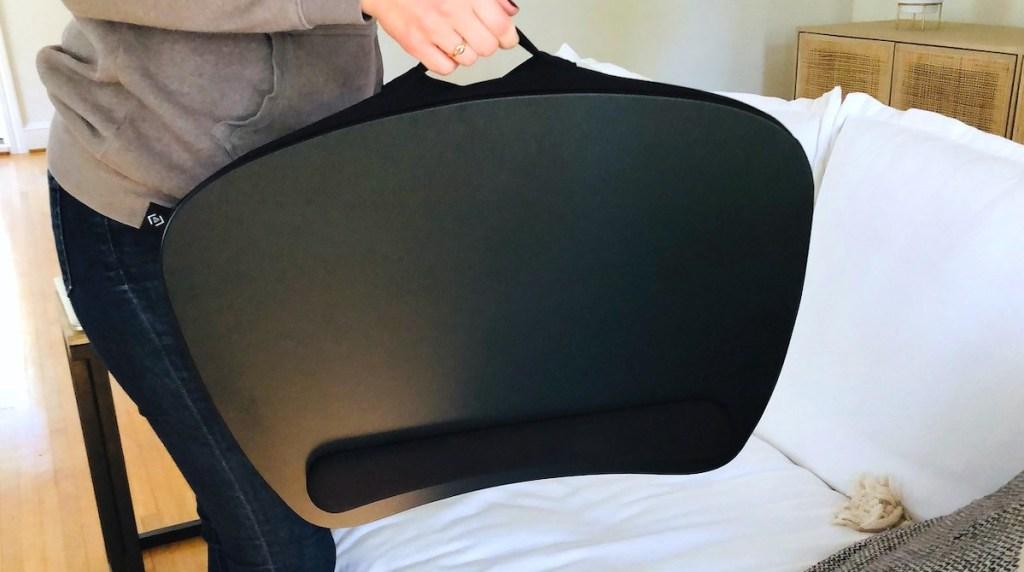 person holding up black lap desk