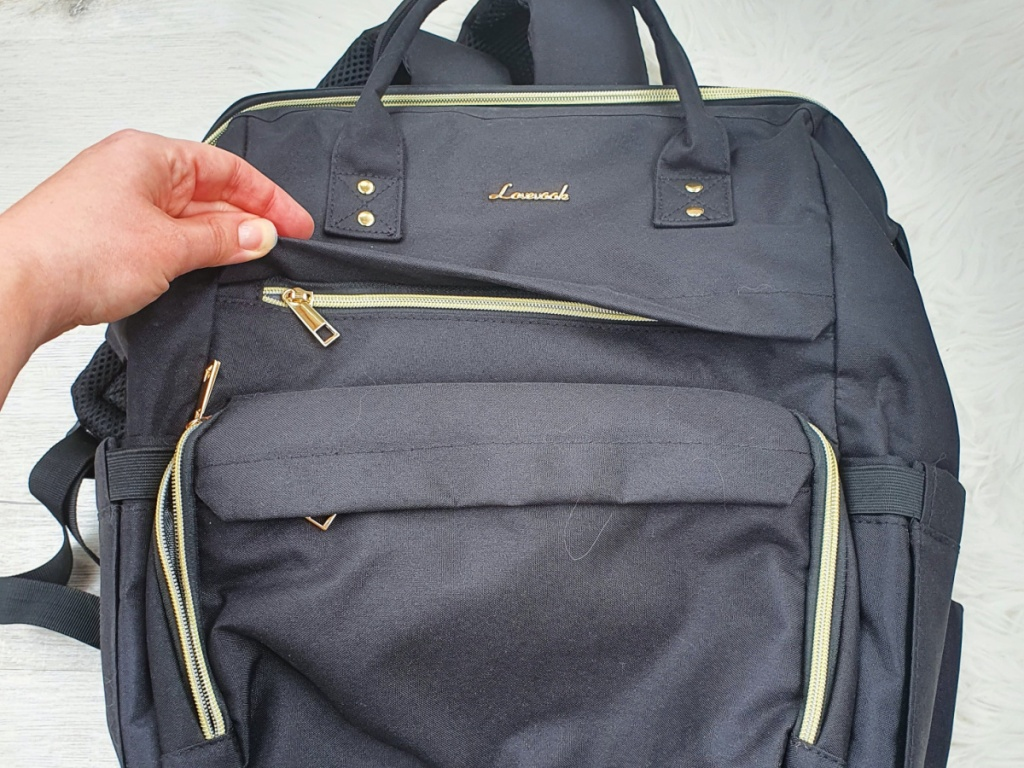 hand opening the pocket of a grey laptop bag